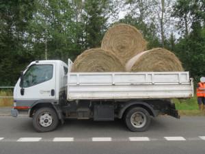 Řidič nedostatečně upevnil náklad, balík slámy spadl na projíždějící auto.